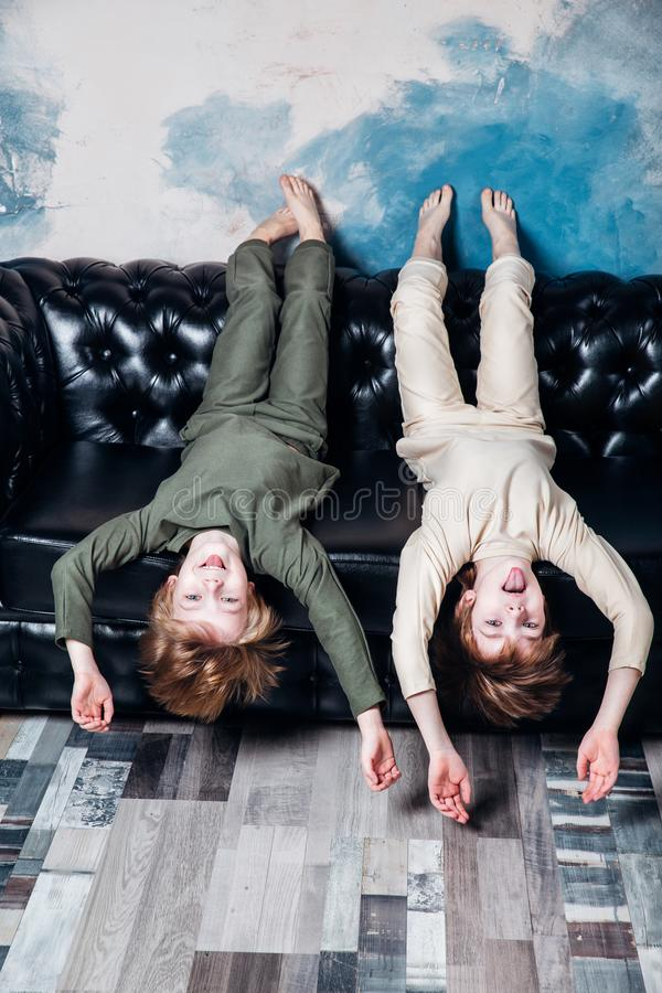 Little twin brothers in pajamas having fun at home room royalty free stock photos