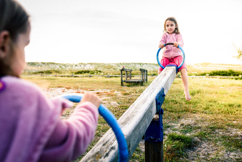 Little twin girls children are riding seesaw swing in park. royalty free stock photography