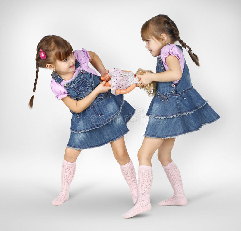 Little twin girls fighting. And shared doll