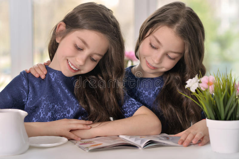 Little twin girls reading a magazine royalty free stock photos