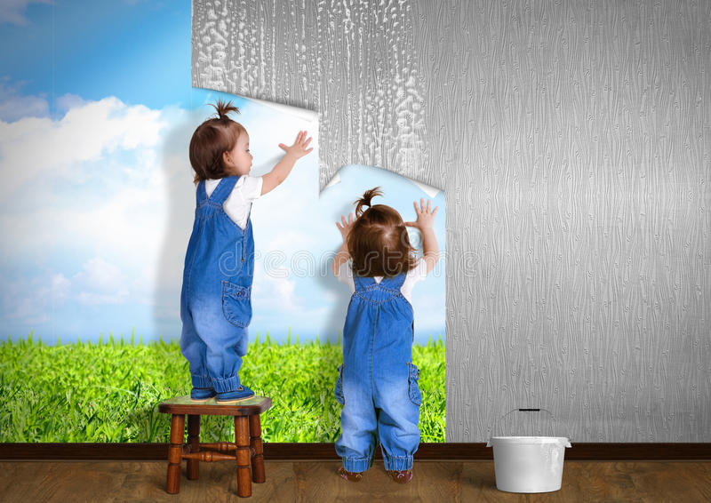 Little twins doing repair at home, hanging wallpaper. Renovation concept royalty free stock photo