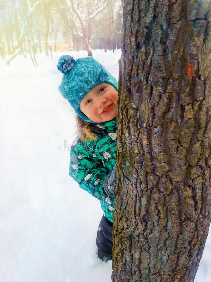 A little boy happily smiles peeking from behind a tree trunk on a winter day. A little two-year-old boy happily smiles peeking from behind a tree trunk on a stock image