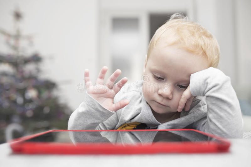 Little two years girl uses a tablet on a sofa royalty free stock photo