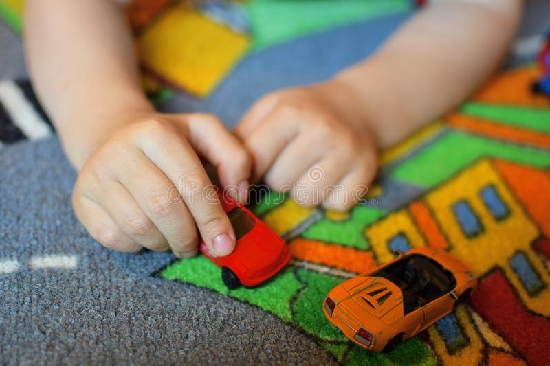 Little child playing with toy car. Little two years old child boy hands playing with red toy car on carpet on floor at home. Shallow depth of field with royalty free stock photo