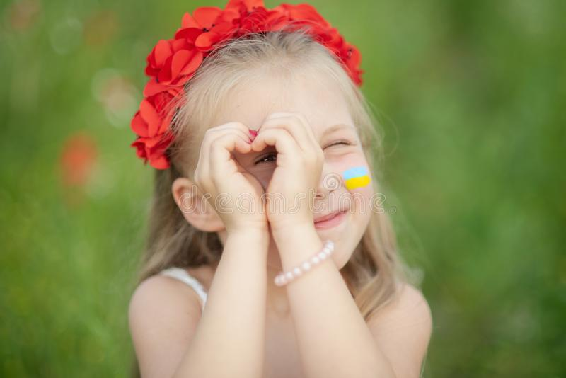 little ukrainian girl looking through heart gesture made with hands in summer green park. Gesture of love to Ukraine by pretty royalty free stock image