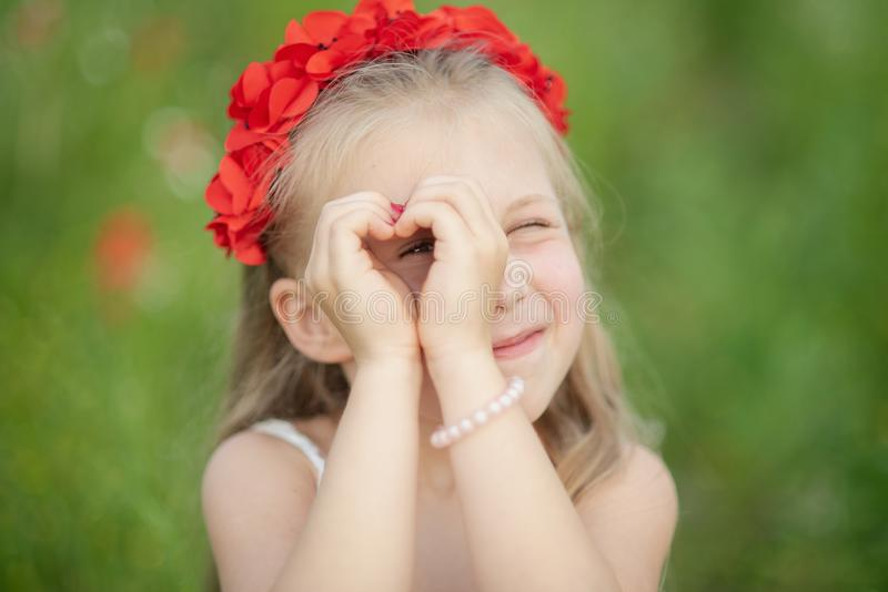 Little ukrainian girl looking through heart gesture made with hands in summer green park. Gesture of love to Ukraine by pretty. Little ukrainian girl looking stock photo