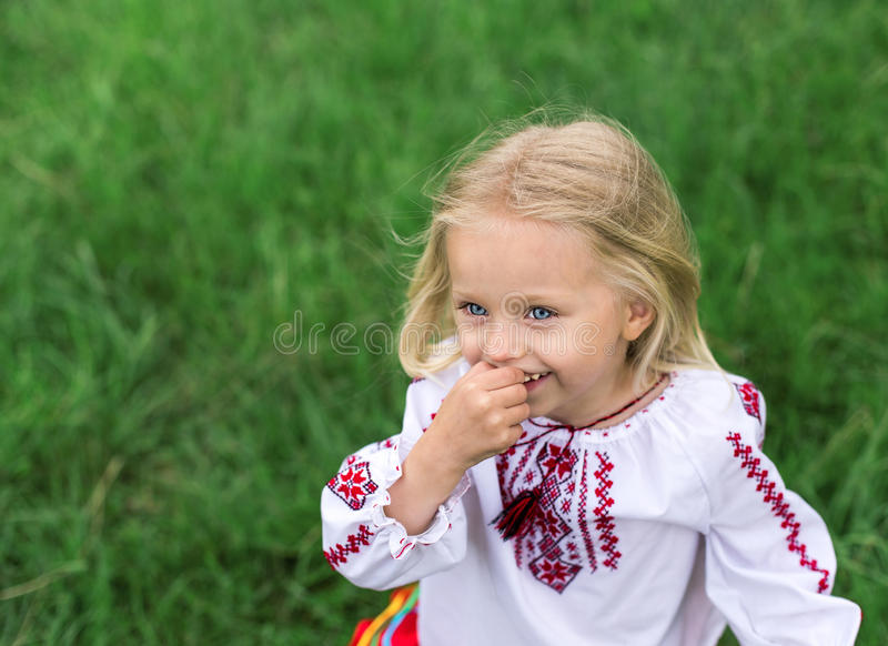 Little ukrainian girl in national costume smiling. Little blonde girl in ukrainian national costume smiling - close up portrait royalty free stock image