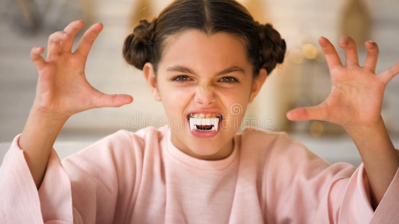 Little vampire girl with big fangs making scary faces at All Hallows Eve party. Stock photo stock photography