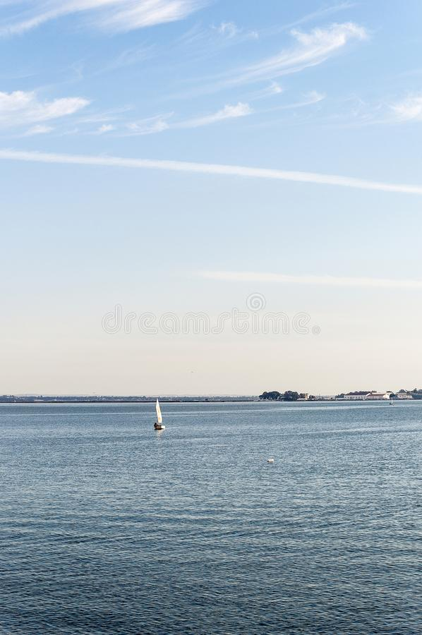The little velero sailing under the sun. Sailboat sailing toward the camera on the blue waters of the bay of Cadíz with La Carraca as background, and slightly royalty free stock photography