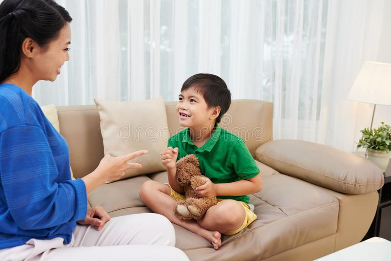 Kid playing with mother stock image