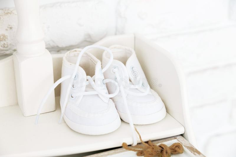 Little white baby shoes on the shelf royalty free stock image