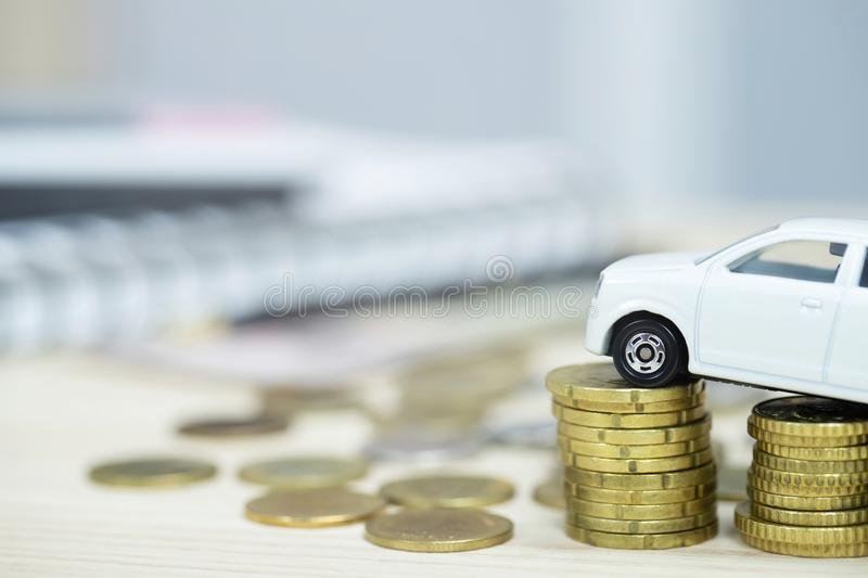 Little White car over a lot of money stacked coins. for bank loans costs finance stock photos