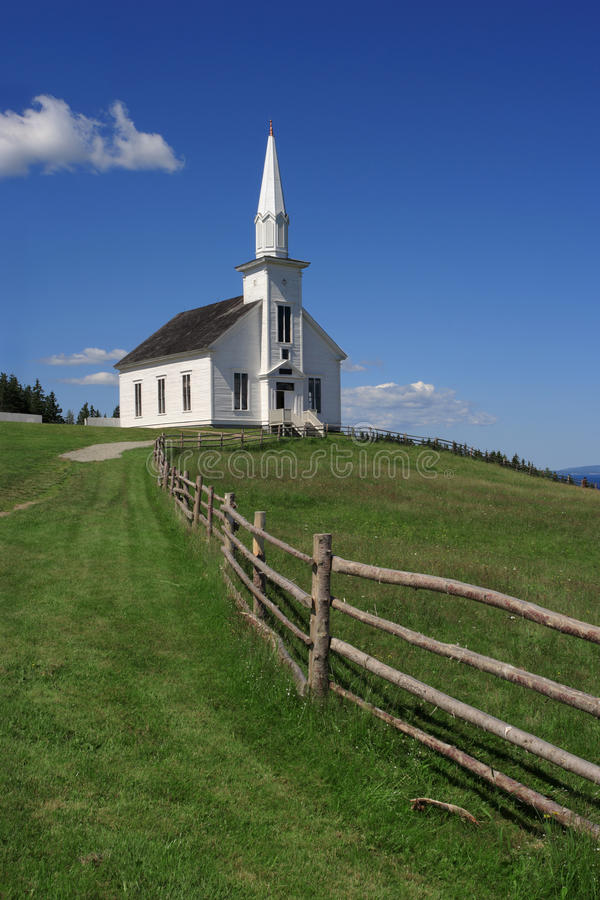 Little white church on a hill. Photo of a little white wooden church in the countryside stock photo