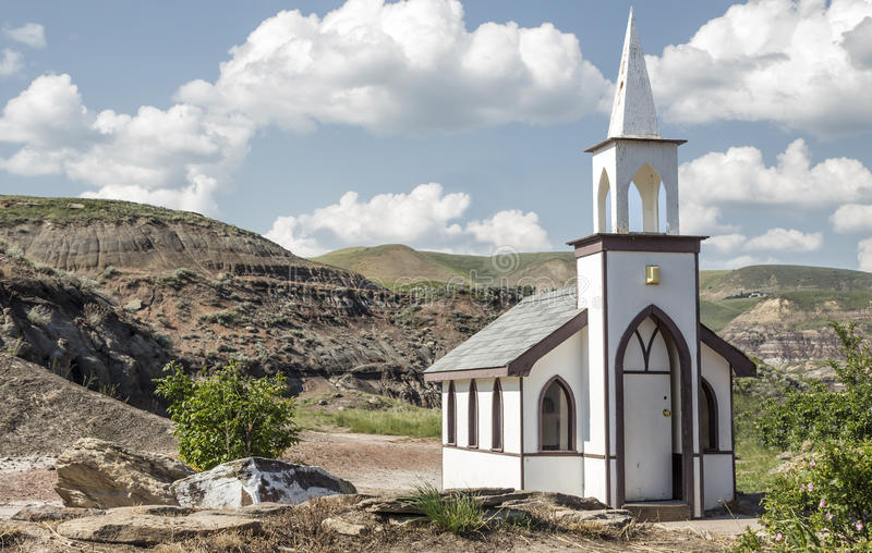 Little white country church. Little white country church nestled in the hills with a blue sky with white clouds on a bright summer day royalty free stock image