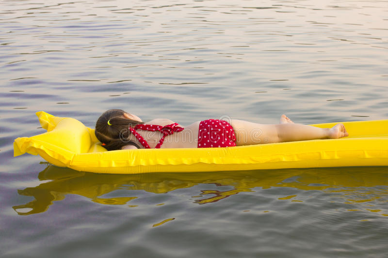 Little white girl children lay on inflatable mattress on lake stock image