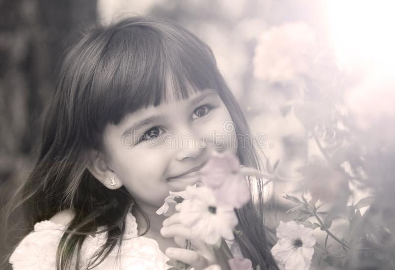 Little white girl with a happy smile near the flowers, Sunny day stock photography