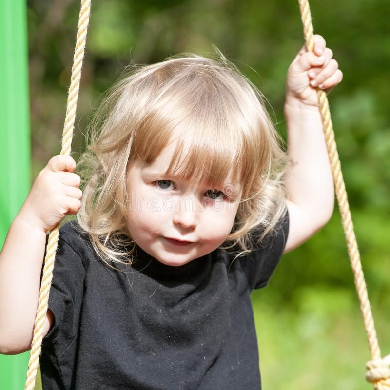 Little white girl sitting on swing board closeup face view royalty free stock photo