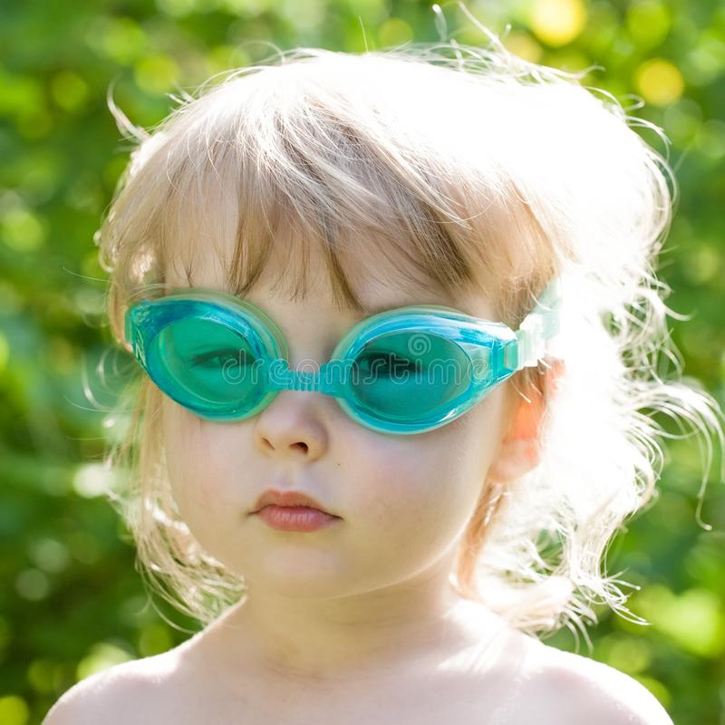 Little white girl in swimming glasses closeup face view royalty free stock photography