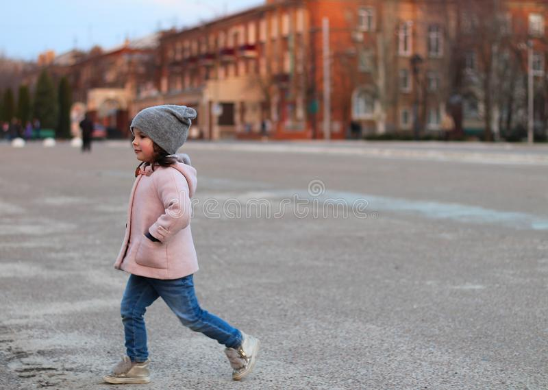 little white girl walking down the street in the evening. Portrait on the background of the sunset cityscape royalty free stock photography