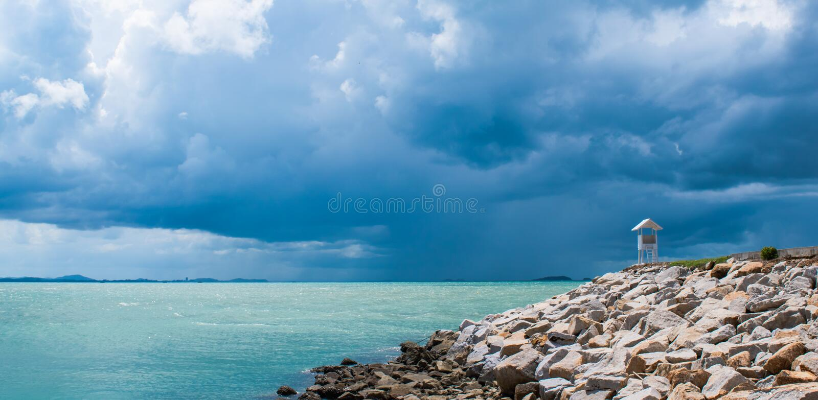 Little white house on the end of sea beach walkway and beautiful dark clouds background at Khao Lam Ya, Rayong, Thailand. royalty free stock images