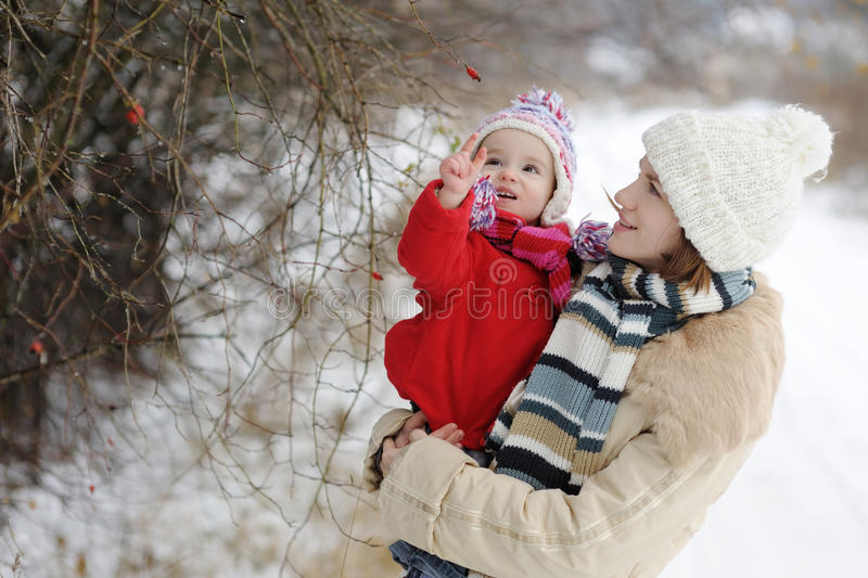 Little winter baby girl and her young mother stock photography