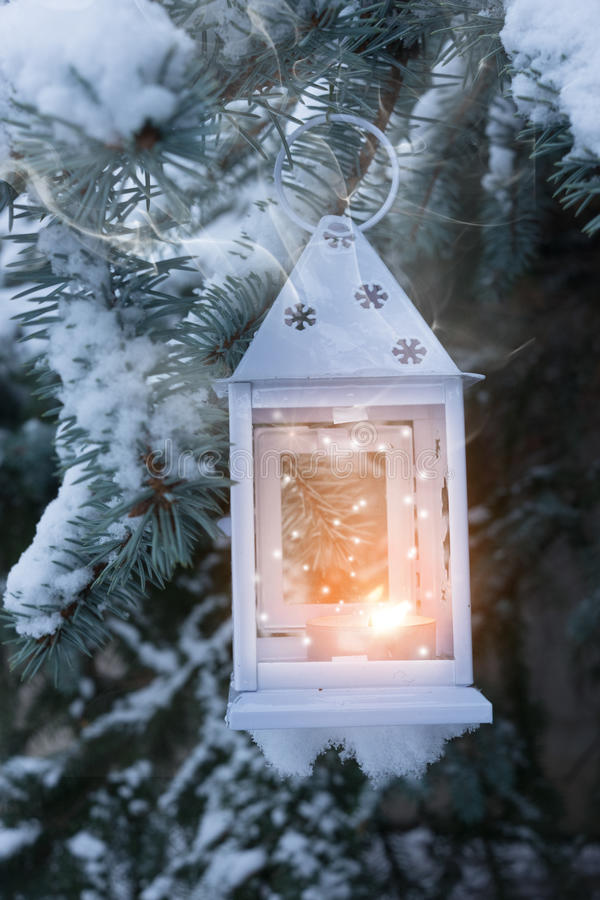 Little winter lantern hanging outdoors on a Christmas tree under stock photo