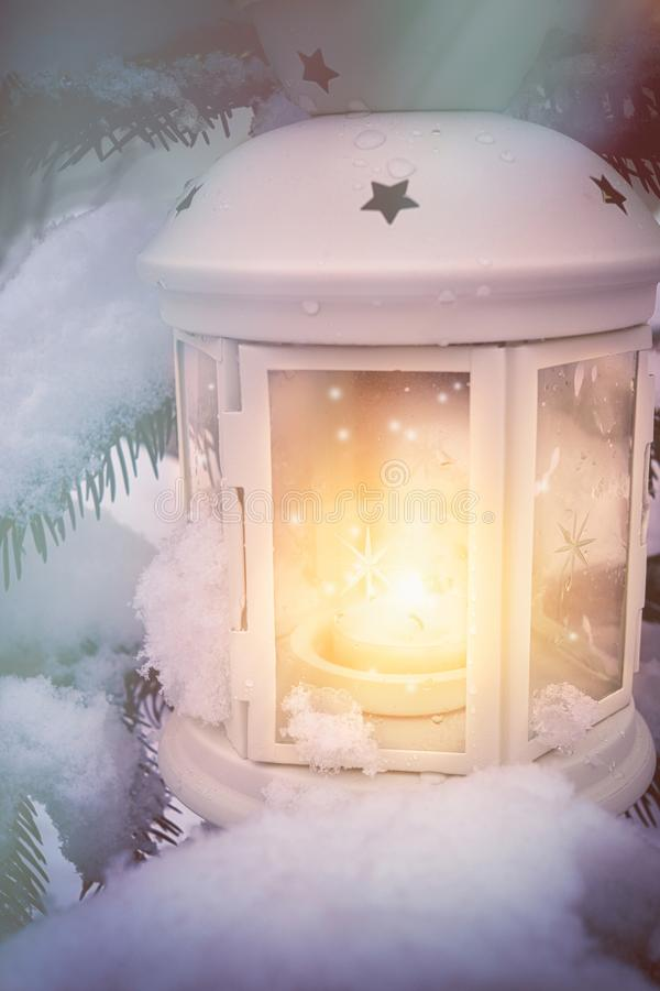 Little winter lanterns outdoors on a Christmas tree under snow stock photo