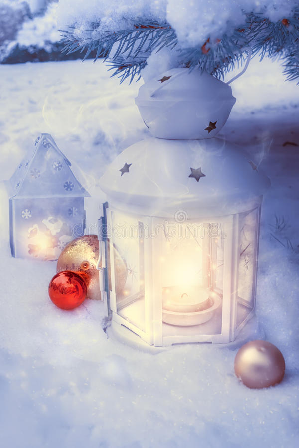 Little winter lanterns outdoors on a Christmas tree under snow. stock photography