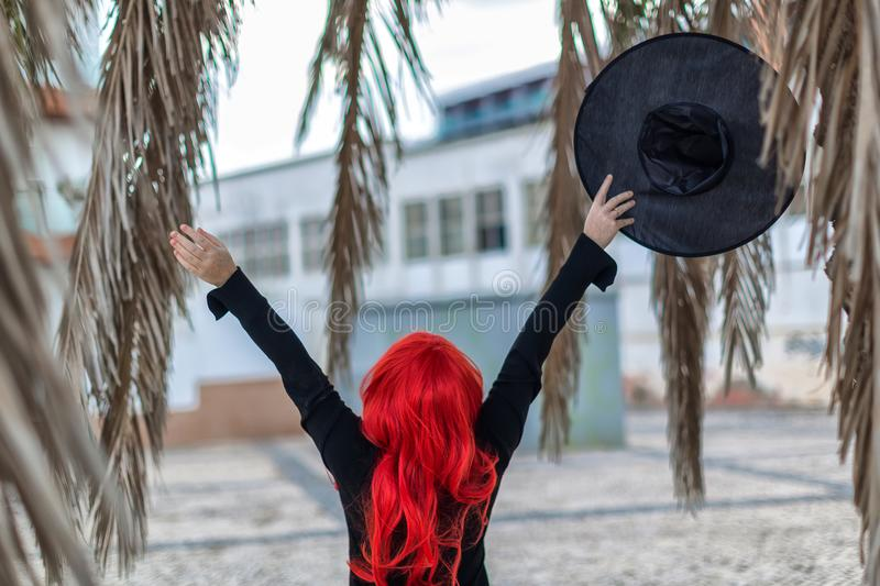 Little witch in a black dress with red hair is holding a hat stock photos