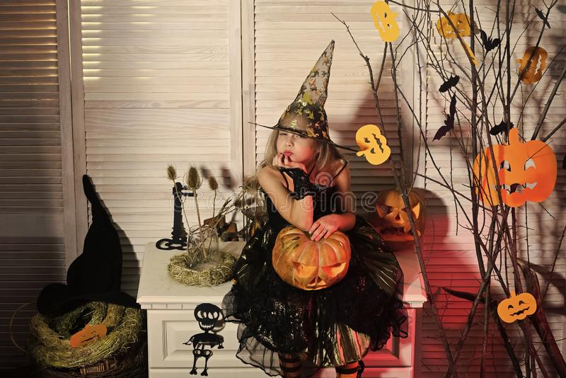 Little witch with Halloween decor. Girl with suspicious face. On spooky carnival room background. Halloween party and celebration concept. Kid in witch hat and stock images
