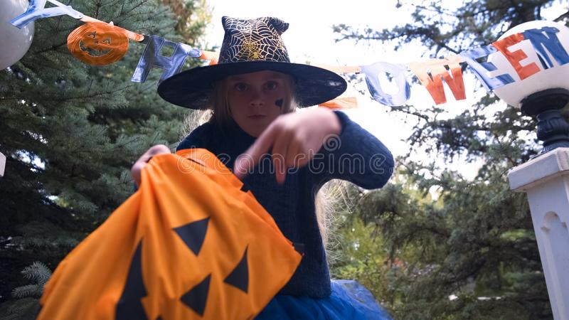Little witch kid demanding sweets, children trick-or-treating, Halloween event stock photography