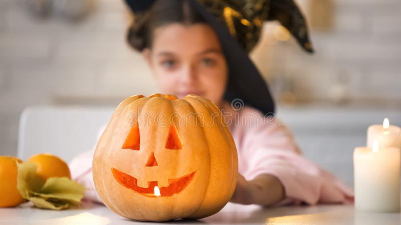 Little witch showing scary Jack-o-Lantern pumpkin, preparing for Halloween party royalty free stock photography