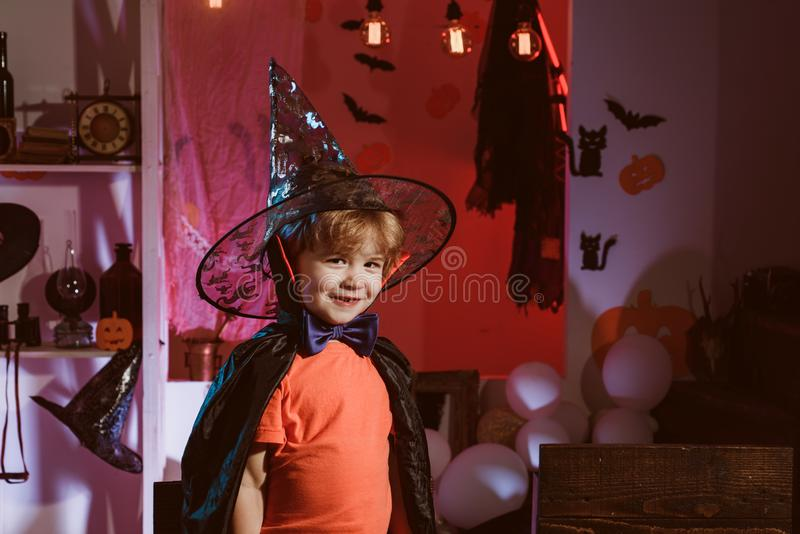 Little wizard for Halloween holiday. Happy child. Boy in wizard hat is ready for Halloween party. stock photography