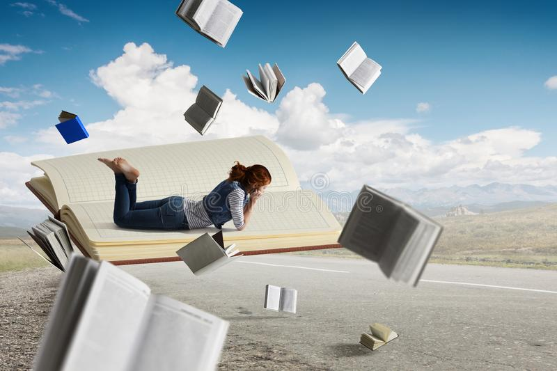 Little woman with large book concept. Little woman lying on a large open notebook, levitating outdoors stock images