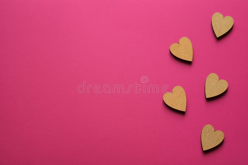 Little wooden hearts on pink background. Romantic composition with copy space for greeting royalty free stock photo