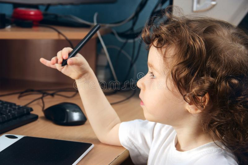 Little 2 3 year old baby girl in white clothers draws at the home computer in graphics drawing tablet. The child is holding a pen royalty free stock images
