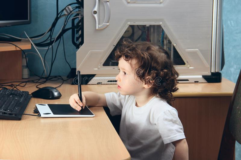 Little 2 3 year old baby girl in white clothers draws at the home computer in graphics drawing tablet. The child is holding a pen royalty free stock photos