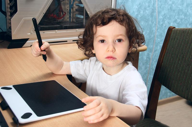 Little 2 3 year old baby girl in white clothers draws at the home computer in graphics drawing tablet. The child is holding a pen stock photo
