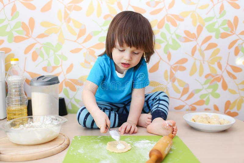 Little 2 years boy bakes sitting on a table at home kitchen royalty free stock photos