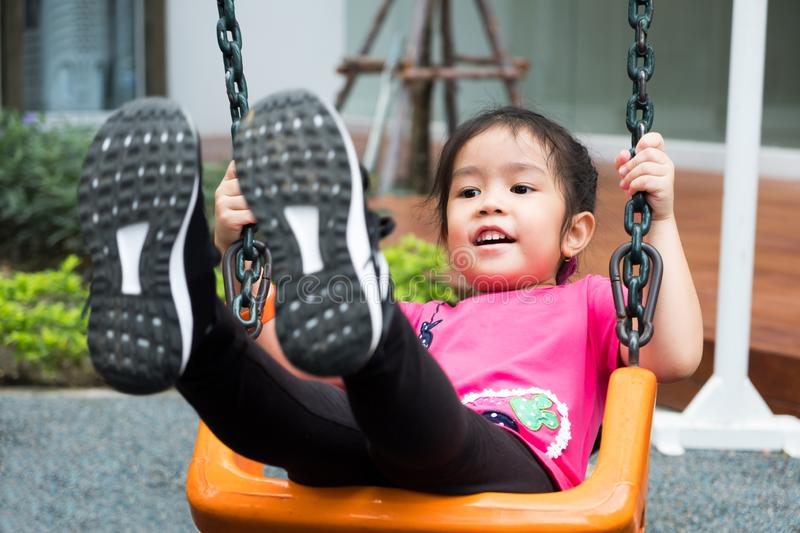 Little 4 years girl wear pink t-shirt playing swing at outdoor playground. kids love to swing. she laughing with happiness feeling royalty free stock images