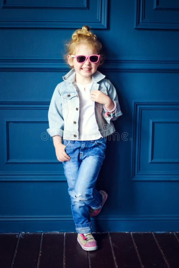 Little 4 years old curly blonde smiling girl in denim jacket, jeans and pink sunglasses stand in blue studio. Hipster lifestyle in royalty free stock image