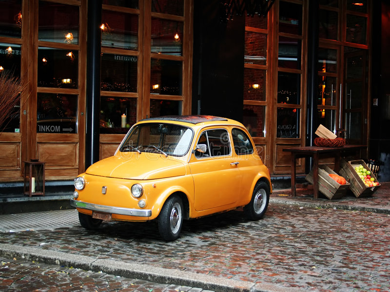 Little yellow fiat car. Little yellow retro fiat car standing in front of a restaurant as eye-catcher royalty free stock images