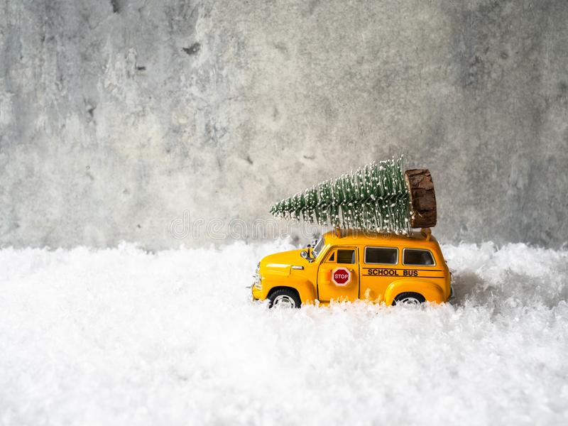 Little yellow toy school bus carries a Christmas tree on the roof stock image