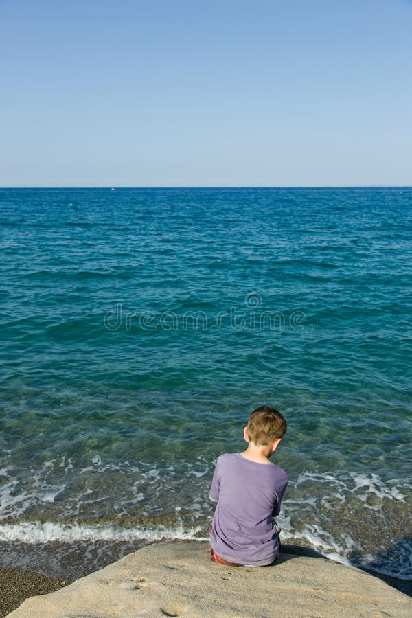 Blue sky and green - blue sea, horizon, silent waves and a little sitting boy can be seen from behind, in foreground coastal rock. stock image