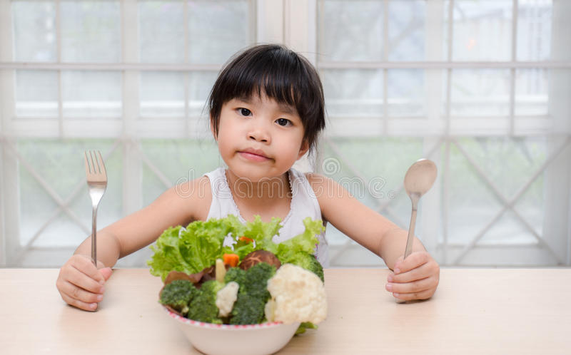Little young cute sweet smiling girl eats fresh salad / healthy eating concept royalty free stock image