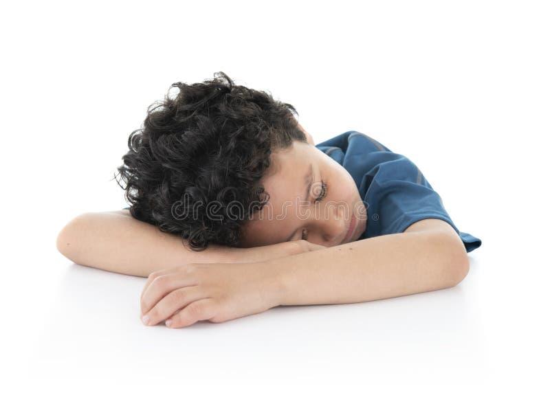 Little Young Exausted Lazy Boy Fell Asov på White Table, Studio Shot, isolerad på vit bakgrund royaltyfria bilder