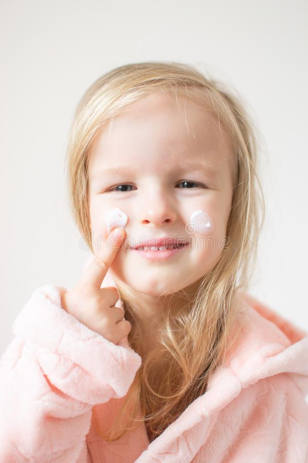 Little young girl applying moisturizing cream on her face. Skin care and beauty concept stock photography