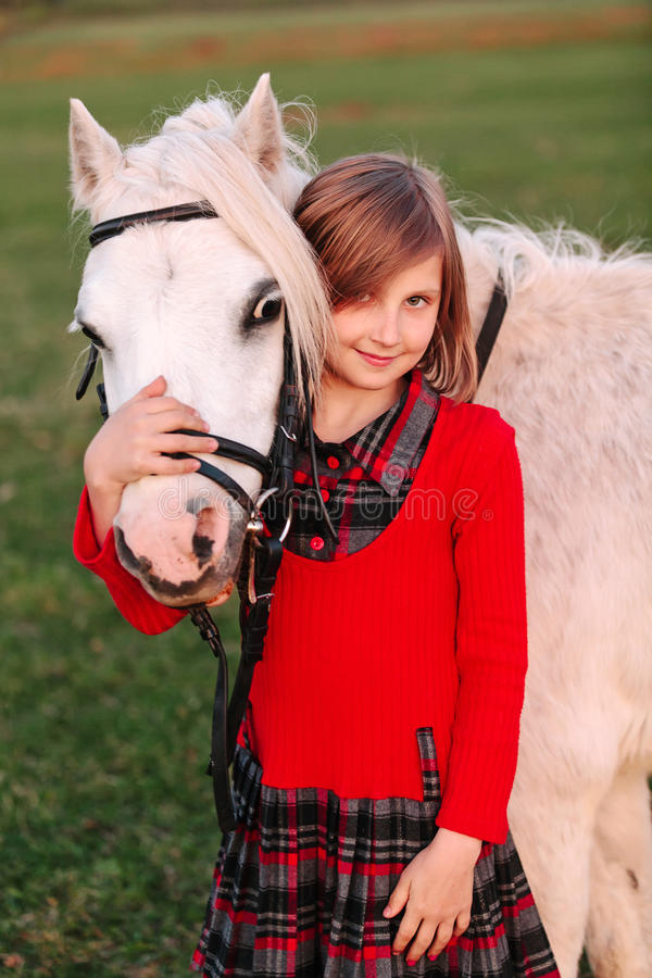 Little young girl child hugging a white pony at his head and smiling royalty free stock photo