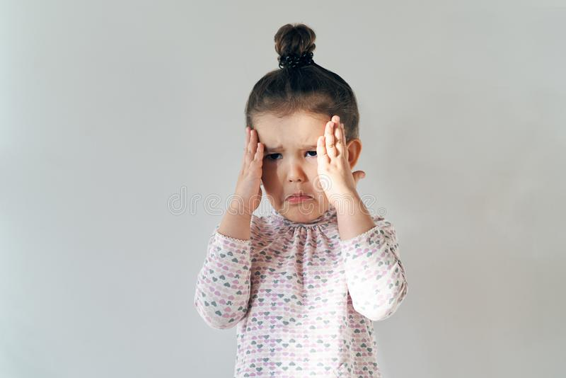 little young girl with her hair gathered on top posing for a portrait in natural light with a disturbed crying expression, by stock photo