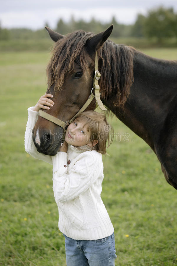 Little young girl in a white pullover and jeans hugged his head to horse's on farm warm autumn day. Lifestyle portrait stock photo